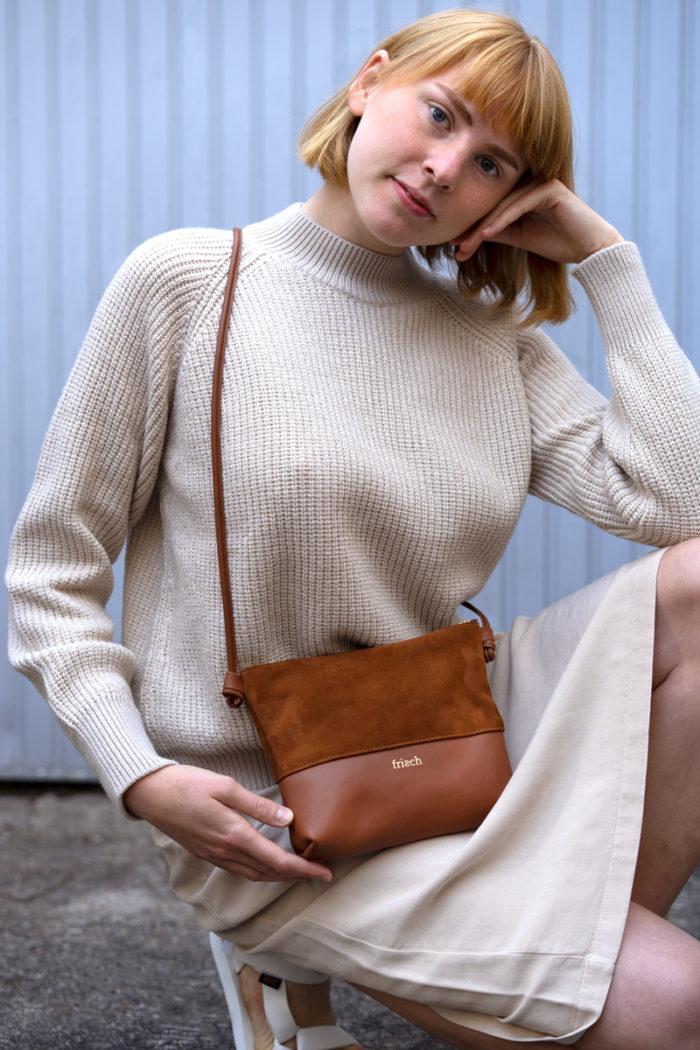 Handtasche ERDE hockend präsentiert von Modell vor blauer Wand