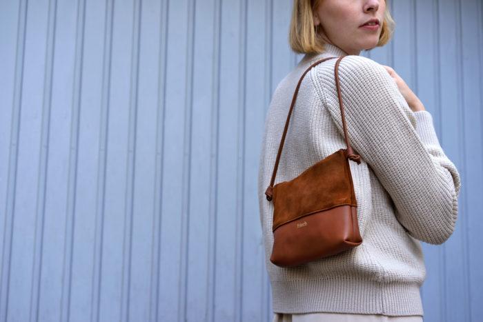 Modell trägt Handtasche Erde aus Glatt- und Veloursleder