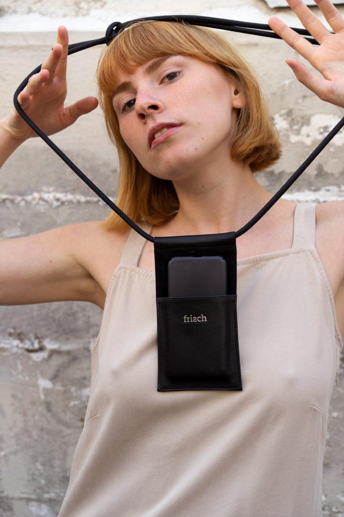 Produktfoto Handtasche aus Leder in schwarz mit silber Prägung mit verstellbarer Kordel an Modell in beigefarbenem Kleid
