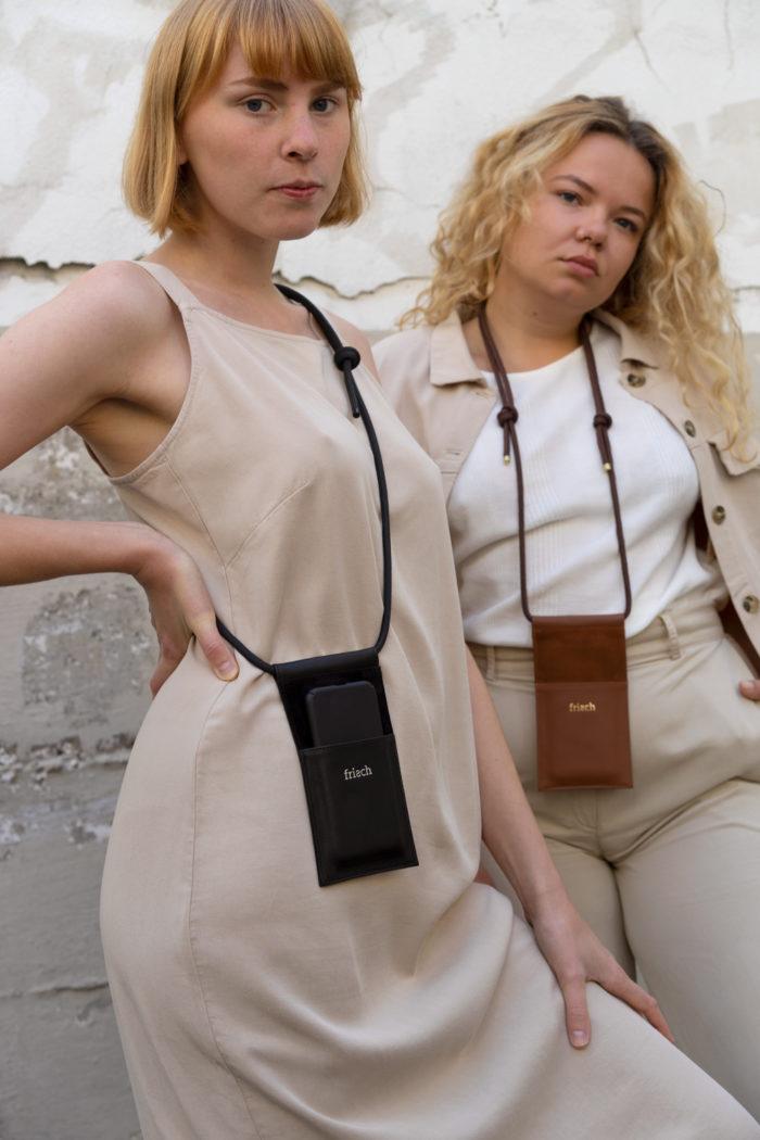 Produktfoto Handtasche aus Leder in schwarz und braun mit verstellbarer Kordel an Modellen